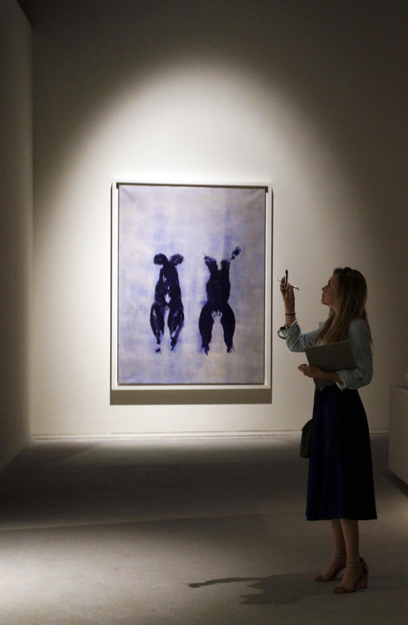 """A journalist takes a photo in front of """"Anthropometry"""" by French artist Yves Klein which is part of a sample collection at the Abu Dhabi branch of the Louvre in Abu Dhabi, United Arab Emirates, Tuesday, April 16, 2013. No artistic subjects will be off limits at the Abu Dhabi branch of the Louvre museum as it builds its collection for a planned 2015 opening, a top overseer said Tuesday, in a city seeking to broaden its international profile but testing how far to open its conservative culture. (AP Photo/Kamran Jebreili)"""
