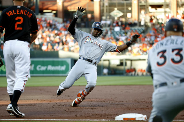 Miami Marlins' Lewis Brinson triples in front of Baltimore Orioles third baseman Danny Valencia (2) and Marlins third base coach Fredi Gonzalez in the second inning of a baseball game, Friday, June 15, 2018, in Baltimore. (AP Photo/Patrick Semansky)