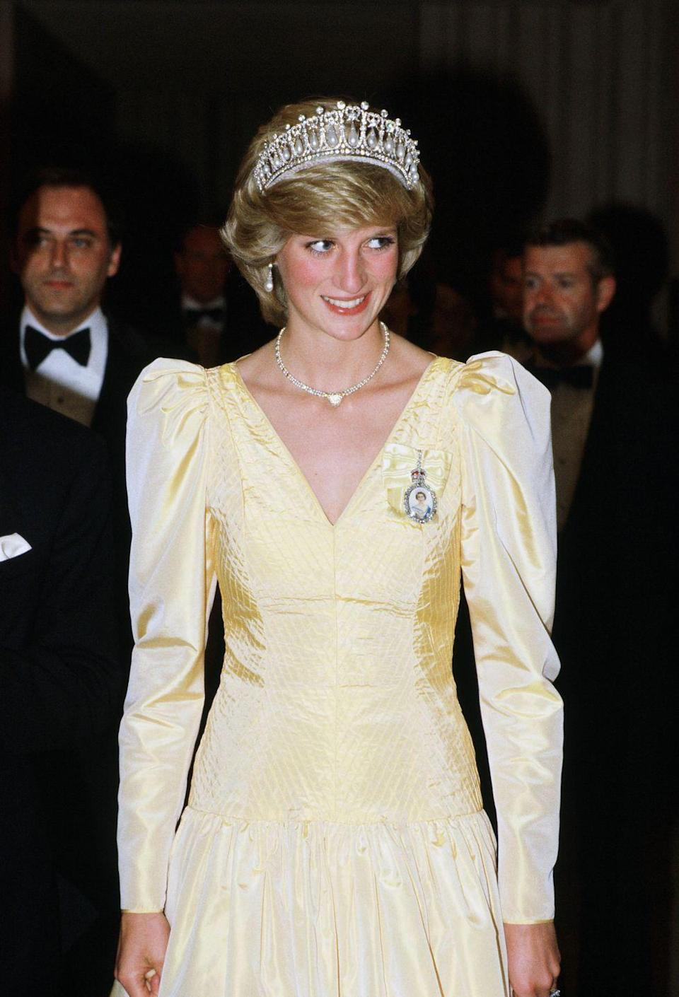 <p>In a yellow satin dress, pearl-and-diamond Cambridge Tiara, and heart-shaped necklace given to her by Prince Charles after the birth of their first son while attending a banquet in Canada.</p>