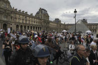 Protesters march in the courtyard of Le Louvre museum during a demonstration against the health pass, Saturday, Aug. 21, 2021 in Paris. People denounce a COVID-19 health pass needed to access restaurant, long-distance trains and other venues. (AP Photo/Adrienne Surprenant)