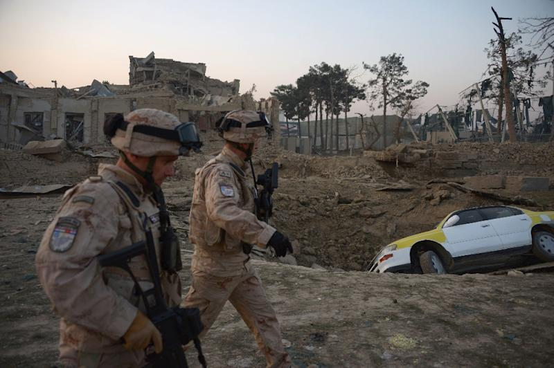 NATO soldiers walk past the site of an attack targeting the German consulate in Mazar-i-Sharif, Afghanistan on November 11, 2016 (AFP Photo/Farshad Usyan)