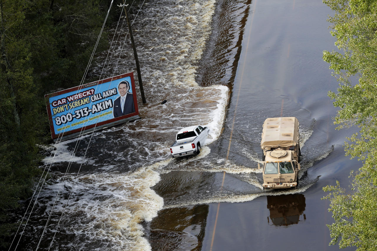 A National Guard vehicle drives past a truck washed off the roadway from floodwaters in Dillon, S.C., Monday, Sept. 17, 2018, in the aftermath of Hurricane Florence. (AP Photo/Gerald Herbert)