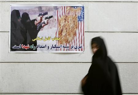 Iranian woman walks past an anti-U.S. poster during a visit to a war museum in Khorramshahr, southwest of Tehran
