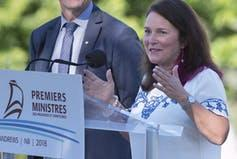 A woman with dark shoulder-length hair speaks into a microphone behind a podium that reads Premiers Ministres.