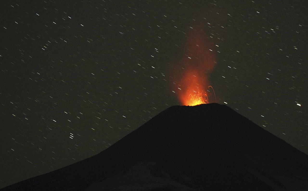 """Smoke and lava spew from the Villarrica volcano, as seen from Pucon town in the south of Santiago March 26, 2015. The Villarrica Volcano expelled smoke as scientists warn the concentration of lava, contained within the structure, is close to the crater. On March 3 a short-lived eruption of ash and rock led to the evacuation of thousands from the nearby area. Authorities have restricted access to the area within 5 kilometres (3 miles) of the crater and have put the area under an orange alert due to the volcano's """"heightened unrest and increased likelihood of eruption."""" REUTERS/Cristobal Saavedra"""
