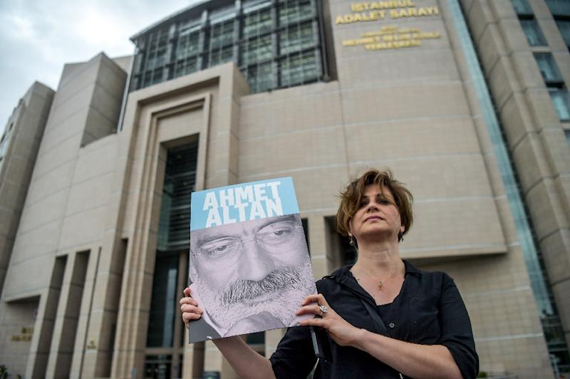 A journalist poses with a portrait of Turkish journalist Ahmet Altan on June 19, 2017 in front of the Istanbul courthouse