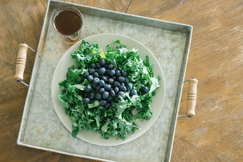 kale salad with blueberries and a glass of tea on an old serving plate