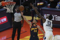 Golden State Warriors' Stephen Curry, left, shoots against Memphis Grizzlies' Jaren Jackson Jr. during the second half of an NBA basketball Western Conference play-in game in San Francisco, Friday, May 21, 2021. (AP Photo/Jed Jacobsohn)