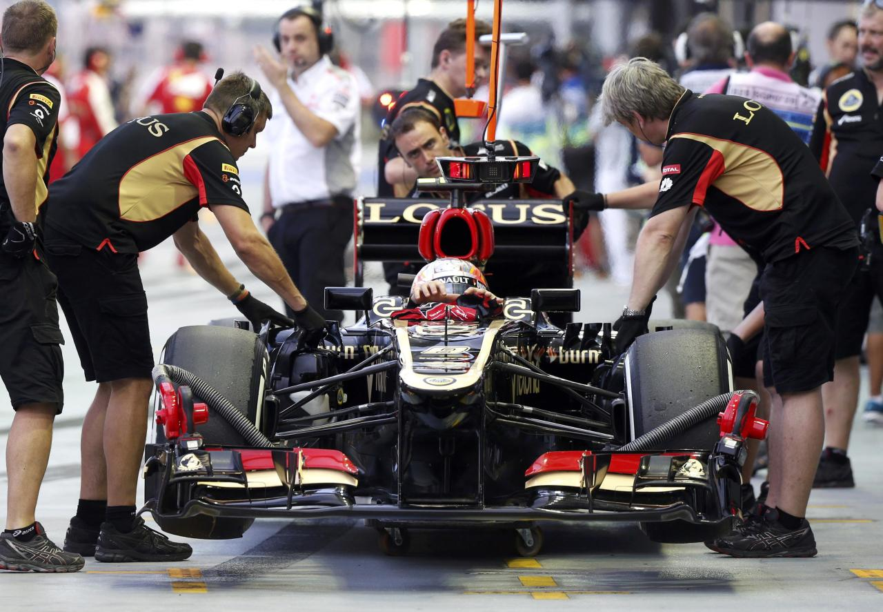 Lotus F1 Formula One driver Romain Grosjean of France removes his gloves as he sits in his car during the third practice session of the Singapore F1 Grand Prix at the Marina Bay street circuit in Singapore September 21, 2013. REUTERS/Pablo Sanchez (SINGAPORE - Tags: SPORT MOTORSPORT F1)