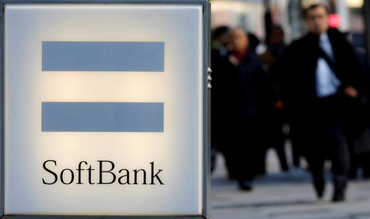 FILE PHOTO - People walk behind the logo of SoftBank Corp in Tokyo