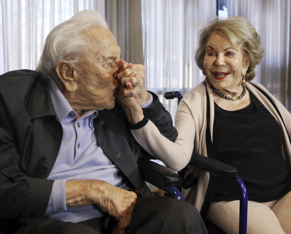 FILE - In this May 4, 2017, file photo, Kirk Douglas kisses his wife Anne's hand, in Los Angeles during a party celebrating his 100th birthday. Anne Douglas, the widow of Kirk Douglas and stepmother of Michael Douglas, died Thursday, April 29, 2021, in California. She was 102. Douglas died at her home in Beverly Hills, according to an obituary provided by spokeswoman Marcia Newberger. No cause of death was given. (AP Photo/Reed Saxon, File)