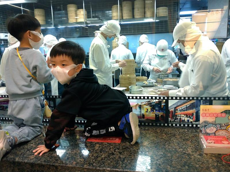 Two children wear face masks to protect against the spread of the coronavirus and watch dumpling making of Din Tai Fung at a department store in Taipei, Taiwan, Saturday, March 7, 2020. (AP Photo Chiang Ying ying)
