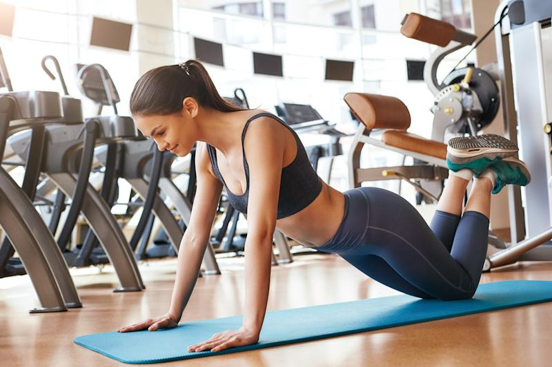 Strong and healthy. Side view of sporty young woman doing push ups while workout at gym. Fitness and sport concept. Healthy lifestyle
