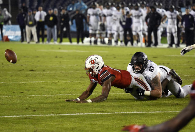 Utah quarterback Jason Shelley (15) fumbles as he is tackled by Northwestern defensive lineman Joe Gaziano (97) as he runs during the second half of the Holiday Bowl NCAA college football game Monday, Dec. 31, 2018, in San Diego. The fumble was picked up by Northwestern and returned for an 86-yard touchdown. (AP Photo/Denis Poroy)