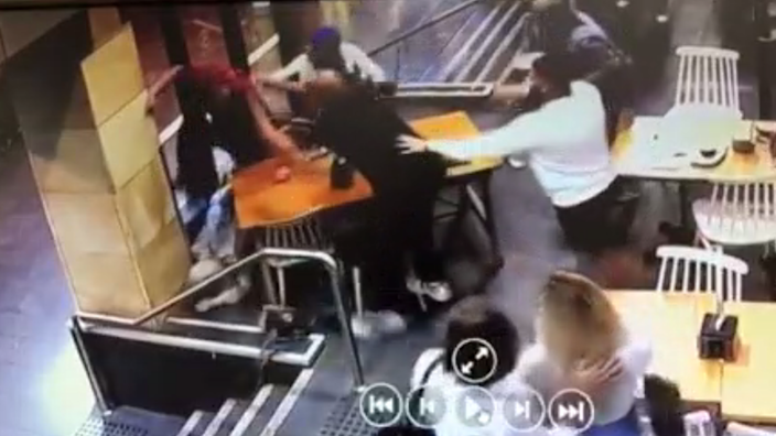 A still from a police video shows other cafe customers pulling Lozina away during his attack on Ms Elasmar
