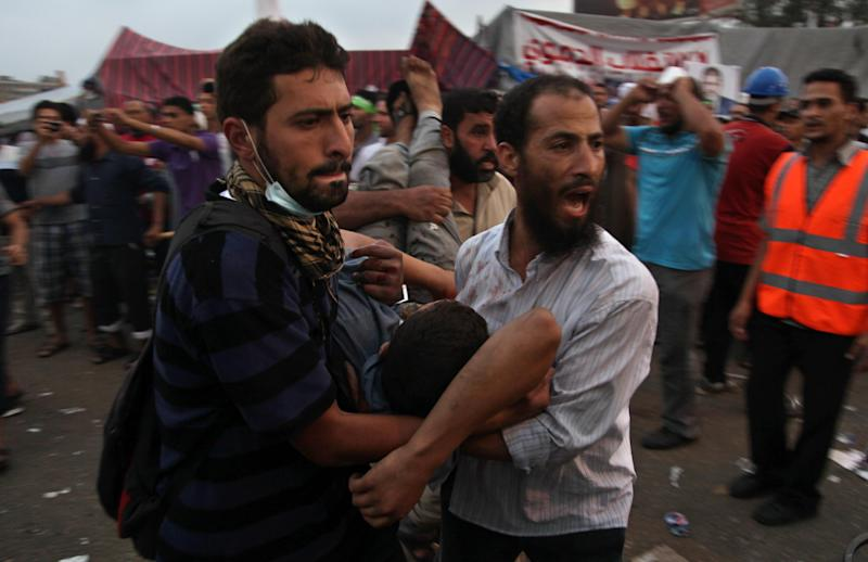 Supporters of Egypt's ousted President Mohammed Morsi carry an injured man to a field hospital following clashes with security forces at Nasr City, where pro-Morsi protesters have held a weekslong sit-in, in Cairo, Egypt, Saturday, July 27, 2013. Police fired tear gas to disperse hundreds of Morsi supporters, setting off clashes that lasted for hours and left tens of people dead. (AP Photo/Khalil Hamra)
