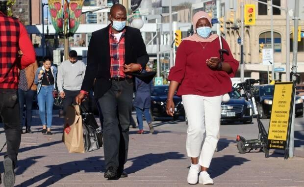 People wearing masks walk through downtown Ottawa on Sept. 26, 2021, during the fourth wave of the COVID-19 pandemic. (Trevor Pritchard/CBC - image credit)