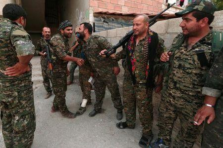 Kurdish fighters from the People's Protection Units (YPG) greet each other in the northeastern city of Hasaka
