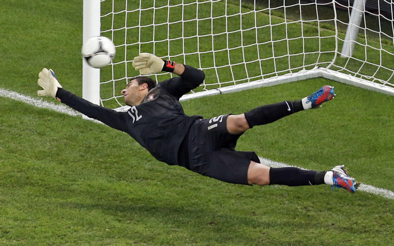 Portugal goalkeeper Rui Patricio fails to save a shot by Spain's Gerard Pique, unseen, in the penalty shootout of the Euro 2012 soccer championship semifinal match between Spain and Portugal in Donetsk, Ukraine, Thursday, June 28, 2012. (AP Photo/Darko Vojinovic)