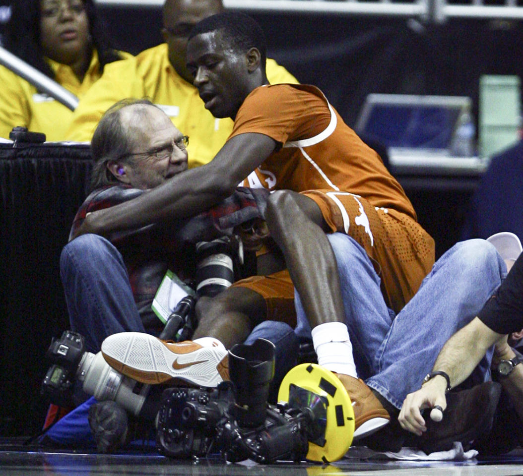 Myck Kabongo #12 of the Texas Longhorns falls into a row of photographers as he chases a loose ball during a game against the Iowa State Cyclones in the quarterfinals of the Big 12 Basketball Tournament March 8, 2012 at Sprint Center in Kansas City, Missouri. (Photo by Ed Zurga/Getty Images)