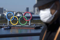 FILE - In this Dec. 1, 2020, file photo, a man wearing a protective face mask to help curb the spread of the coronavirus walks with the Olympic rings in the background in the Odaiba section in Tokyo. Opposition to the Tokyo Olympics is growing with calls for a cancellation as virus cases rise in Japan. The International Olympic Committee and local organizers have already said another postponement is impossible, leaving cancellation, or going ahead, as the only options. (AP Photo/Eugene Hoshiko, File)