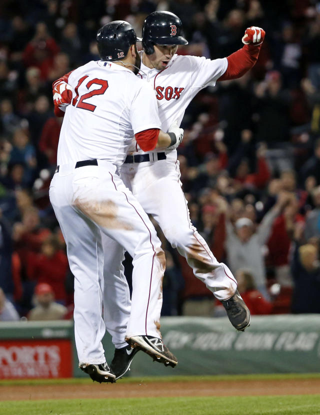Boston Red Sox center fielder Grady Sizemore, right, jumps into the arms of first baseman Mike Napoli (12) to celebrate his walk-off single to defeat the Cincinnati Reds 4-3 in the 12th inning of a baseball game at Fenway Park in Boston, Tuesday, May 6, 2014. (AP Photo/Elise Amendola)