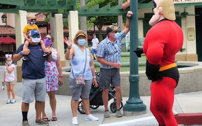 Guests wave to Mr. Incredible at Walt Disney World in Florida, the state at the epicentre of the US outbreak - Joe Burbank/Orlando Sentinel