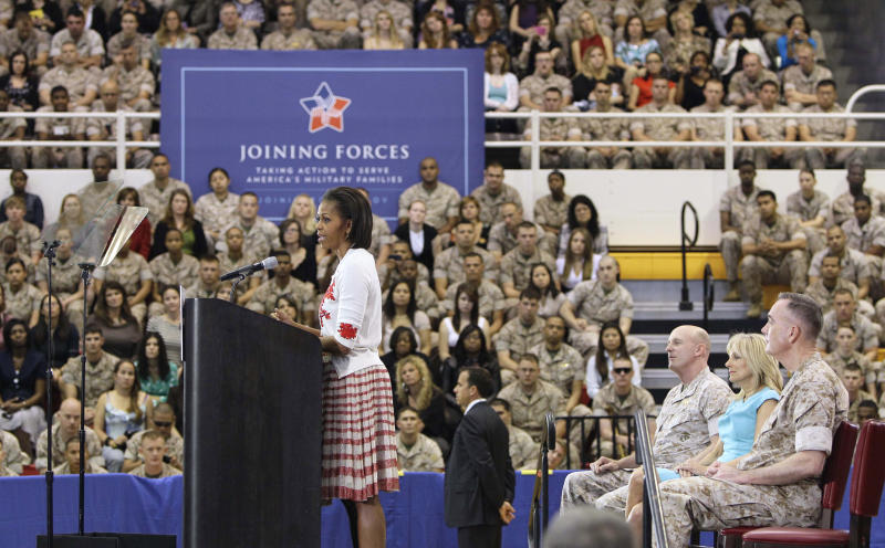 First lady Michelle Obama speaks to Marines at a military community event during a national initiative to support and honor America's service members and their families. Wednesday, April 13, 2011, at Camp Lejeune, N.C. Jill Biden, wife of Vice President Joe Biden sits at right with Maj. Gen. Carl Jenson and Gen. Joseph F. Dunford, Jr., right. (AP Photo/Gerry Broome)