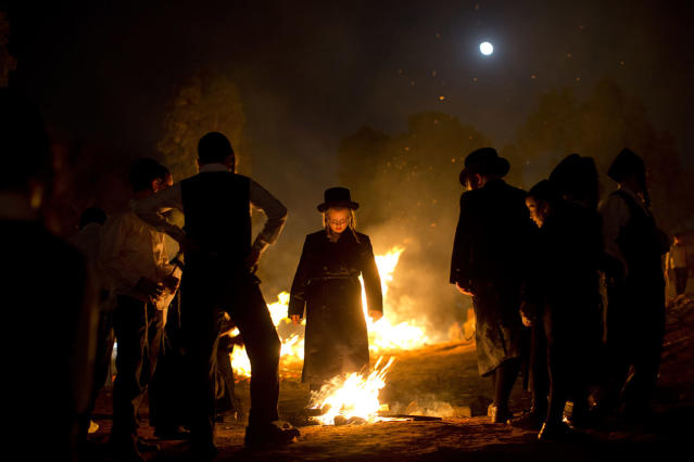 <p>Ultra-Orthodox Jews stand next to bonfires during Lag Ba'Omer celebrations in Bnei Brak, Israel, on May 13, 2017. Lag Ba'Omer commemorates the end of a plague said to have decimated Jews in Roman times. (Photo: Oded Balilty/AP) </p>