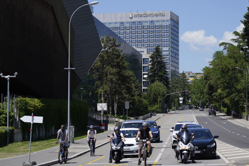 Bikes and cars stand in front of a traffic light near the Hotel Intecontinental in Geneva, Switzerland Monday, June 14, 2021. US President Joe Biden will sleep in the hotel ahead of the meeting with Russian President Vladimir Putin, which is scheduled for Wednesday, June 16, 2021 in Geneva. (AP Photo/Markus Schreiber)