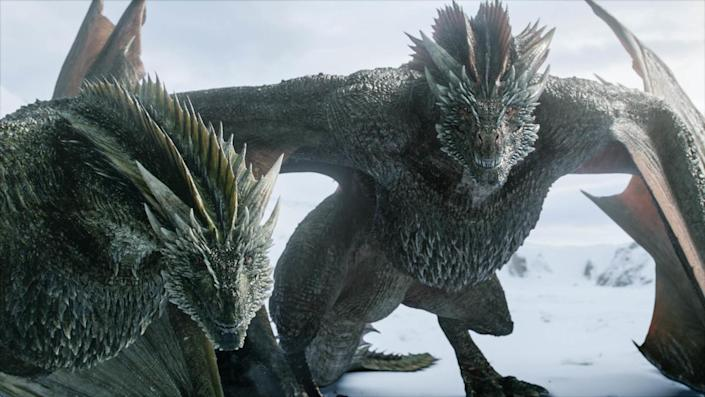 Two dragons stand in the snow on Game of Thrones.
