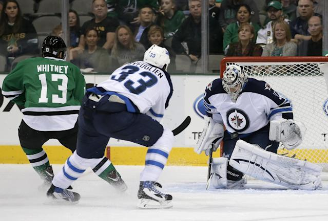 Winnipeg Jets goalie Ondrej Pavelec (31), of Czech Republic, blocks a shot from Dallas Stars left wing Ray Whitney (13) as the Jets' Dustin Byfuglien (33) assists on the pressure in the first period of an NHL hockey game, Saturday, Oct. 26, 2013, in Dallas. (AP Photo/Tony Gutierrez)