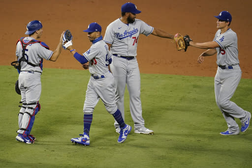 Los Angeles Dodgers' Austin Barnes, Mookie Betts, Kenley Jansen and Corey Seager, from left, celebrate the team's 6-5 win over the Los Angeles Angels in 10 innings in a baseball game Saturday, Aug. 15, 2020, in Anaheim, Calif. (AP Photo/Marcio Jose Sanchez)