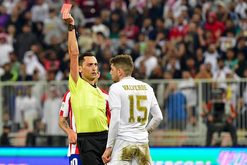 Spanish referee Jose Maria Sanchez Martinez (L) presents a red card to Real Madrid's Uruguayan midfielder Federico Valverde during the Spanish Super Cup final between Real Madrid and Atletico Madrid on January 12, 2020, at the King Abdullah Sports City in the Saudi Arabian port city of Jeddah. (Photo by Giuseppe CACACE / AFP) (Photo by GIUSEPPE CACACE/AFP via Getty Images)