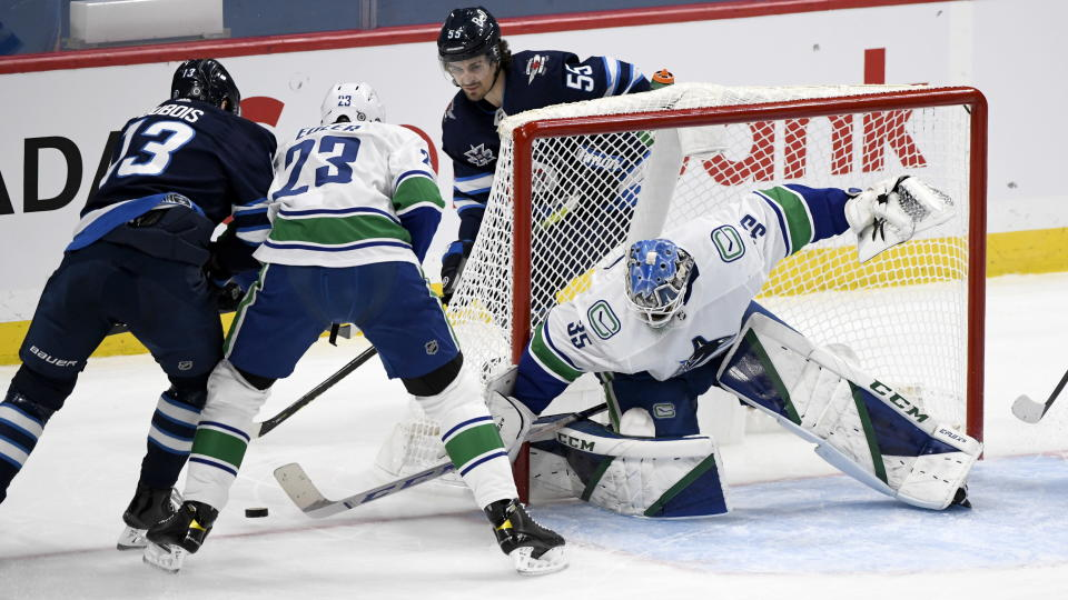 Vancouver Canucks goaltender Thatcher Demko (35) makes a save on Winnipeg Jets' Pierre-Luc Dubois (13) as Canucks' Alexander Edler (23) defends during first period NHL hockey action in Winnipeg, Manitoba on Tuesday March 1, 2021. (Fred Greenslade/The Canadian Press via AP)
