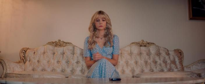 """Cassandra (played by Carey Mulligan) sits on a gaudy couch in her parents' home in """"Promising Young Woman"""""""