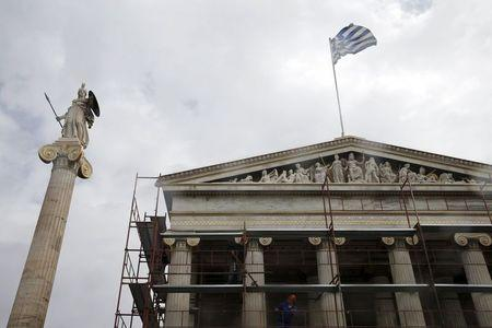 Workers remove scaffolding from the Athens Academy building next to a statue of Goddess Athena