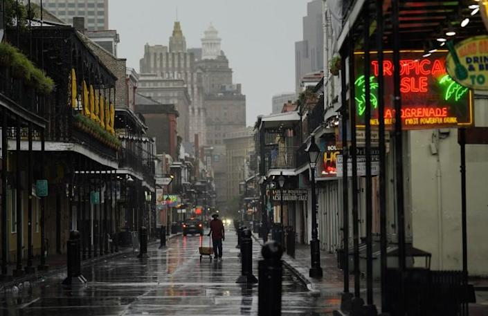 A man pulls a cart down a mostly deserted Bourbon Street in the French Quarter
