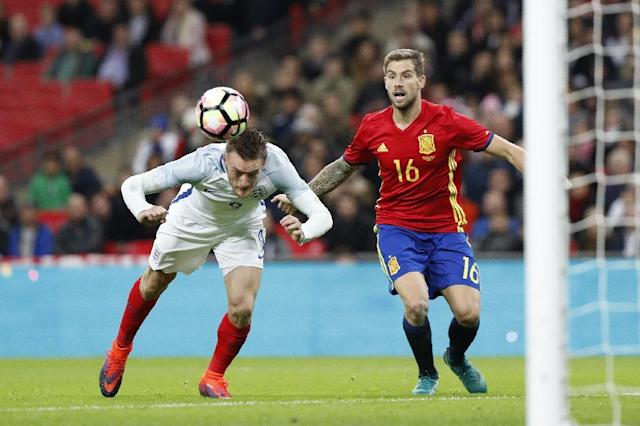 England's striker Jamie Vardy (L) dives past Spain's defender Inigo Martinez to score his team's second goal during the friendly international football match between England and Spain at Wembley Stadium, north-west London, on November 15, 2016 (AFP Photo/Adrian Dennis)