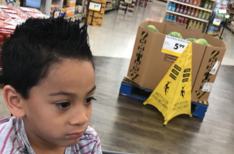 Noah sits in shame in a shopping cart near the scene of the crime. The Caution Wet Floor sign marks where he dropped a watermelon. (Photo: @MiaPulido04 via Twitter)