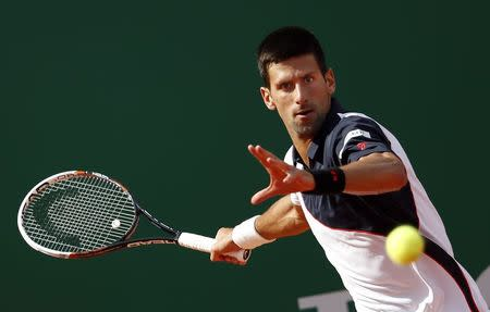 Novak Djokovic of Serbia returns the ball to Pablo Carreno-Busta of Spain during the Monte Carlo Masters in Monaco April 17, 2014. REUTERS/Eric Gaillard