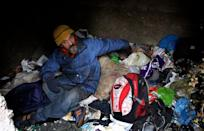 Homeless Bratislav Jovanovic hunkers down inside a grave on January 10, 2013. He lives there during the harsh Serbian winter. Only twelve towns in Serbia have homeless shelters, but these cannot keep up with demand, a homeless volunteer said