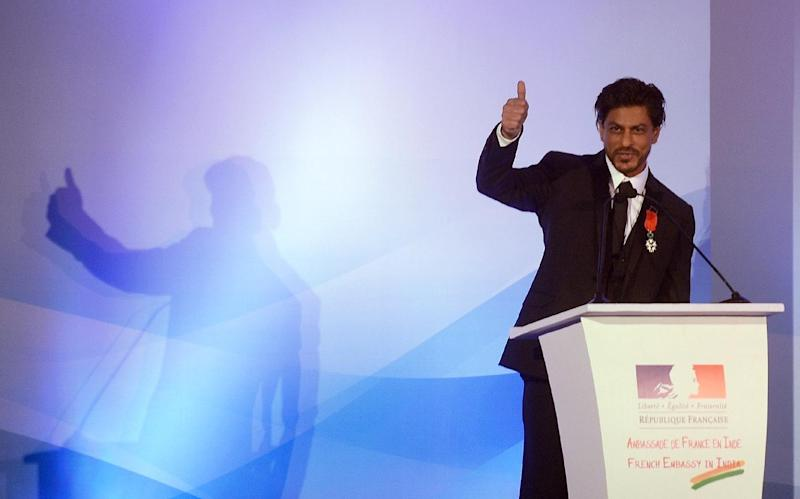 Bollywood star Shah Rukh Khan gestures after being awarded with the Chevalier de la Legion d'Honneur title by French Foreign Minister during a function in Mumbai on July 1, 2014