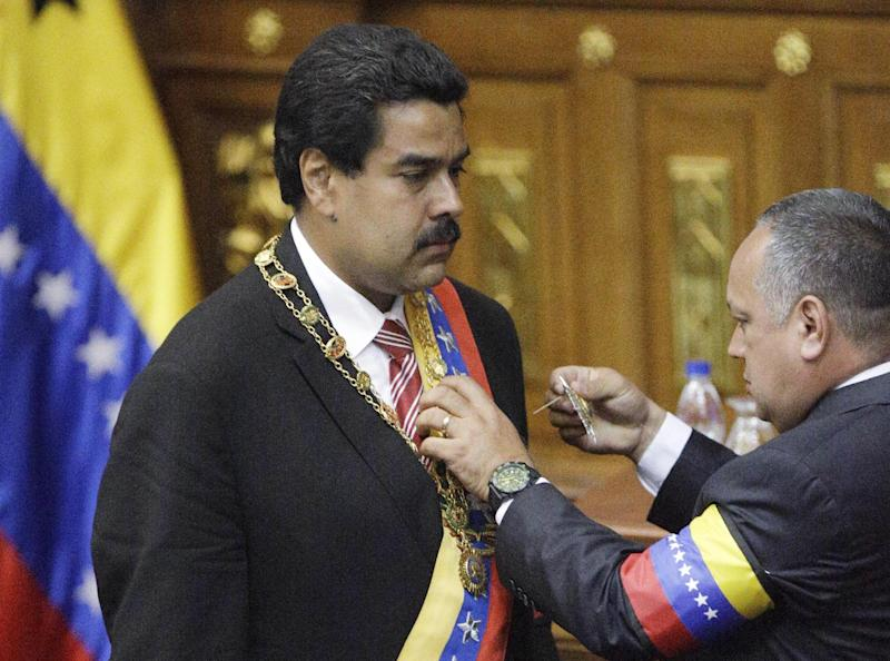 The President of the National Assembly Diosdado Cabello, right, decorates Nicolas Maduro after swearing him in as Venezuela's acting president at the National Assembly in Caracas, Venezuela, Friday, March 8, 2013. Maduro was sworn in Friday as Venezuela's acting president, against the objections of the political opposition who said the move violated the country's constitution. Late President Hugo Chavez designated vice-president Maduro as his successor before he died Tuesday of cancer. (AP Photo/Fernando Llano)