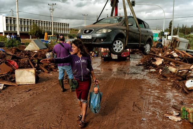 <p>A woman gestures as a car is removed from the road in the town of Mandra, northwest of Athens, on Nov. 15, 2017, after heavy overnight rainfall in the area caused damage and left seven people dead. (Photo: Valerie Gache/AFP/Getty Images) </p>