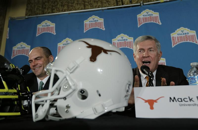 Oregon coach Mark Helfrich, left, and Texas coach Mack Brown, right, take part in a Valero Alamo Bowl news conference, Thursday, Dec. 12, 2013, in San Antonio. Texas and Oregon will play in the NCAA college football game Dec. 30. (AP Photo/Eric Gay)