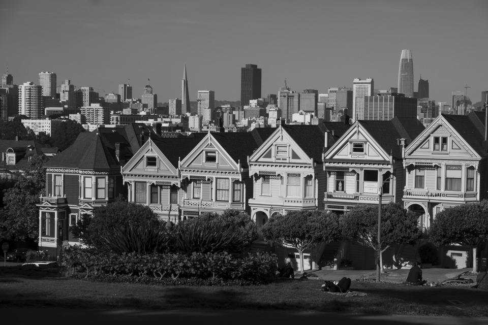 """The """"Painted Ladies"""" Victorian homes sit with the skyline in the background in San Francisco on May 7, 2020. Normally, the months leading into summer bring bustling crowds to the city's famous landmarks, but this year, because of the coronavirus threat they sit empty and quiet. Some parts are like eerie ghost towns or stark scenes from a science fiction movie. (AP Photo/Eric Risberg)"""