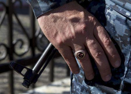 A policeman wears a ring showing the Islamic symbol of the star and crescent, as the barrel of a rifle is seen in the background, in the Chechen village of Itum-Kale, Russia, in this April 29, 2013 file photo. To match story RUSSIA-CHECHNYA/ REUTERS/Maxim Shemetov/Files