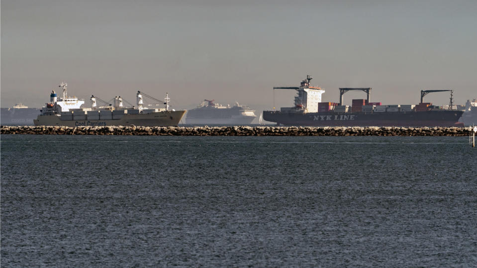 In this Feb. 19, 2021 photo, high number of container ships, a cruise ship, and a small sail boat, dot the coast of Long Beach waiting to dock at the Ports of Los Angeles and Long Beach off the California Coast. A trade bottleneck born of the COVID-19 outbreak has U.S. businesses waiting for shipments from Asia _ while off the coast of California, dozens of container ships have been anchored, unable to unload their cargo. (AP Photo/Damian Dovarganes)