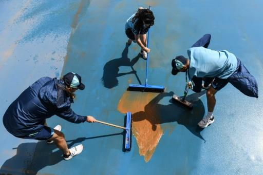 Workers had to clean the courts after they were left muddy from the rain
